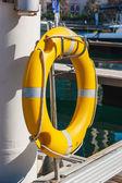 Bouée de sauvetage jaune sur le quai de la mer — Photo
