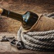 Bottle of wine wrapped with rope - Stock Photo
