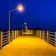 Pier at night with yellow lights on a background of blue sky — Stock Photo #21745679