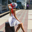 Girl in a hat with a suitcase going on rest - Stock Photo