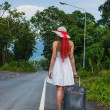 Royalty-Free Stock Photo: Girl with a suitcase on a deserted road