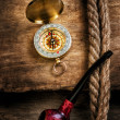 Compass and a pipe with a rope — Stock Photo #23729921