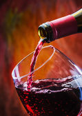 Wine pours into the glass of the bottle — Stock Photo