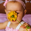 Stock Photo: Little girl smelling the perfume of a wild flower