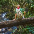Traveler with a backpack on a log in the jungle — Stock Photo #25667715