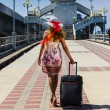 Girl in a hat with a suitcase going on rest — Stock Photo #27328643