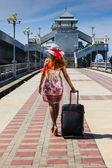 一顶帽子带下去休息着手提箱的女孩 — 图库照片
