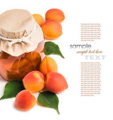 Apricot jam in a glass jar with ripe bright apricots on a white — Stock Photo