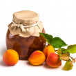 Apricot jam in a glass jar with ripe bright apricots on a white — Stock Photo #29589239
