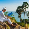 The man  in a white suit and hat sitting on a rock on the sea ba — Stock Photo