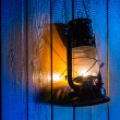 Old kerosene lantern hanging on the yellow wooden wall — Foto de Stock