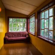 Empty spacious veranda with windows and a sofa — Photo