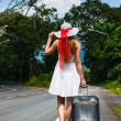 Girl with a suitcase on a deserted road — Foto Stock