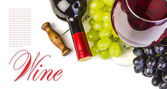 Glass of red wine with bottle and grapes — Stock Photo