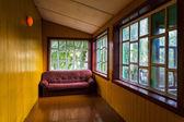 Empty spacious veranda with windows and a sofa — Stock Photo