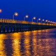 Pier at night with yellow lights on a background of blue sky — Stock Photo #29997167