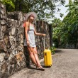 Girl with a yellow suitcase on a resort — Stock Photo