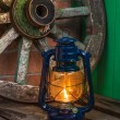 Kerosene lamp  against the background wagon wheel — Zdjęcie stockowe