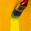 Paintbrush with yellow paint dye wooden wall — Stock Photo