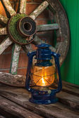 Kerosene lamp against the background wagon wheel — Stock Photo