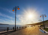 Street lights on the promenade of great river — Stock Photo