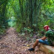 Travelling man sitting in the bamboo forest — Stock Photo