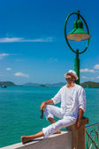 The man in a white suit and hat sitting on a rock on the sea background — Stockfoto