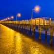 Pier at night with yellow lights on a background of blue sky — Stock Photo