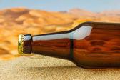 Bottle of beer in desert — Stock Photo