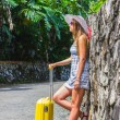 Girl with a yellow suitcase on a resort — Stock Photo #39623493