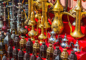 Row of shiny traditional coffee pots and lamp — Photo