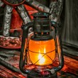 Kerosene lamp  against the background wagon wheel — Stock Photo #45348235