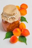 Marillenmarmelade im glas mit reif hell aprikosen auf einem weißen — Stockfoto