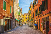 Narrow canal among brick houses in Venice — Stock Photo