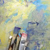 Paint brushes lying on artwork — Stock Photo