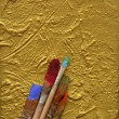 Paint brushes lying on artwork — Stock Photo