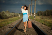 Young fashion girl with suitcase at railways — Stock Photo