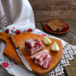 Bacon and bread on an old board. — Stock Photo