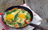 Fried eggs with greens on a frying pan. — Stock Photo