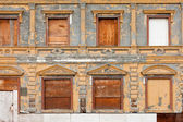 Boarded up derelict building facade peeling paint — Stock Photo