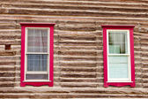 Red framed windows in log house wall architecture — Stock Photo
