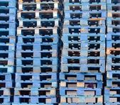 Piled blue wooden euro pallets background pattern — Stock Photo