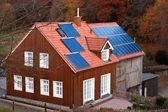 Casa com sol de painéis solares, aquecimento sistema de telhado — Fotografia Stock