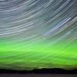 Stock Photo: Star trails and Northern lights in night sky