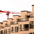 Facade of new apartment building and tower crane — Stock Photo