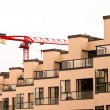 Facade of new apartment building and tower crane — Stock Photo #21691033
