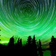 Star trails around Polaris and Northern lights — Stock Photo