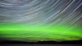 Star trails and Northern lights in night sky — Stock Photo