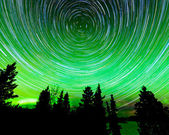 Stjärna spår runt polaris och norrsken — Stockfoto