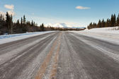 Winter on country road in taiga and snowy mountain — Stock Photo
